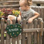 Kind spielt am Zaun