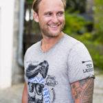 Blonder Mann mit grauem T-Shirt