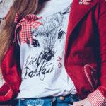 Rote Trachtenjacke, weißes T-Shirt mit Motiv und blaue Trachtenjeans